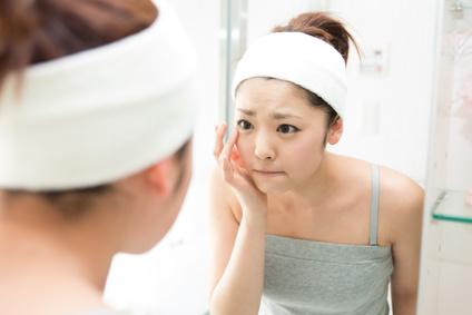 鏡を見て肌のカサつきを気にする女性