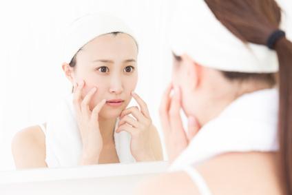 洗顔後に肌の突っ張りを感じ鏡で確認する女性