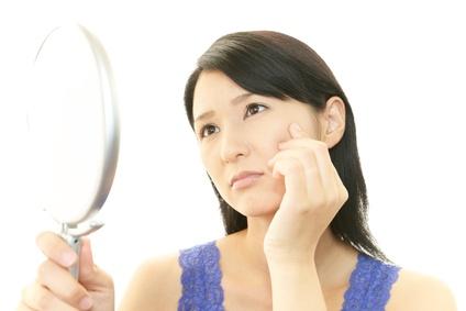 鏡を見て顔のシミやたるみを気にする女性