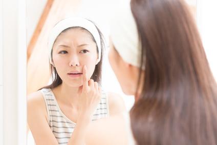 洗面台の鏡で突っ張った肌を確認する女性