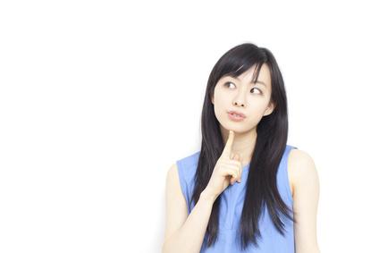 顎に人差し指を当て考え込む女性