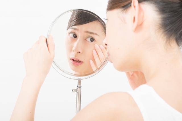 手鏡で肌を確認している女性