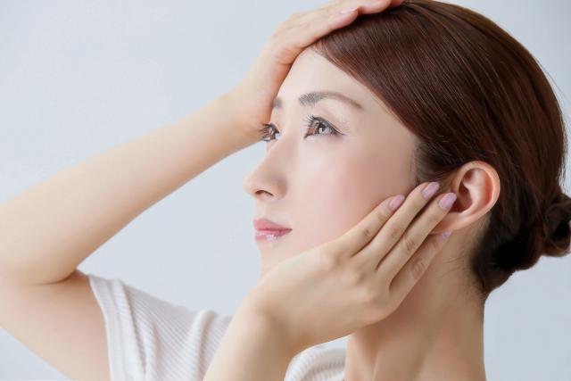 手のひらで顔を覆っている女性の横顔