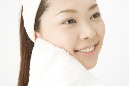 フェイスタオルで顔を拭く女性